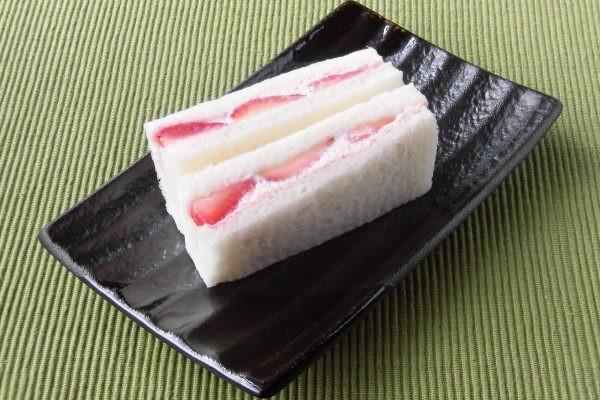 真っ赤ないちごとピンク色のホイップを挟み込んだ白いパン。