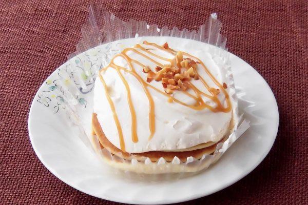 パンケーキ3枚の上にたっぷりのクリームと、線がけになったソースにナッツの飾りつけ。