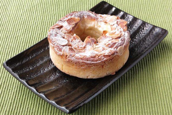 ドーナツ状の生地の表面がアメフィリングで覆われ、スライスアーモンドと粉砂糖が散らしてあります。