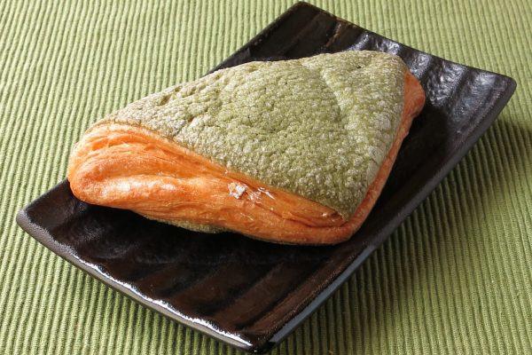 緑色のクッキー生地に覆われた、三角形のデニッシュ生地。