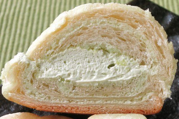 薄緑のメロン生地が巻き込まれたクロワッサンにサンドされた、薄緑のホイップ。