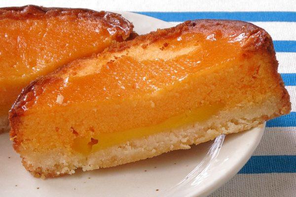 ざっくりしたタルト生地とオレンジ色のケーキ生地の間に黄色いクリーム。